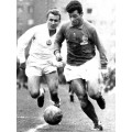 Photo du grand Just Fontaine avec le maillot de foot de France des années 50 sur le terrain de jeu.